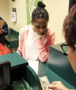 A student participating in the Lessons For Life program withdrawing money from the bank in Weinberg Village.