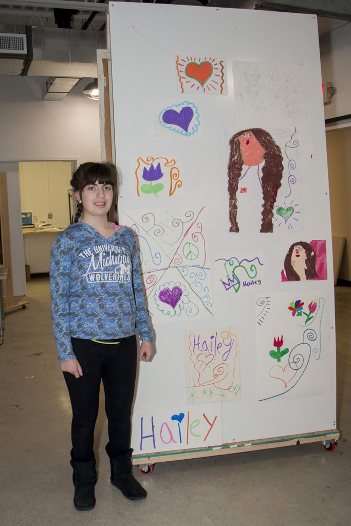 Hailey Reinke next to her Wall of Art
